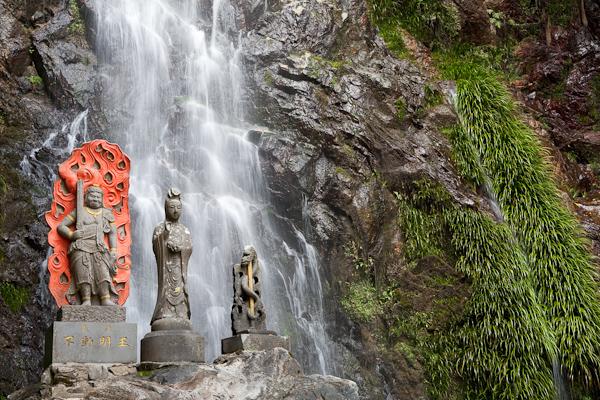 Статуи на фона на водопад при манастира Оги